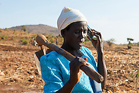 MALAWI, village Zingiziwa, woman with hoe and mobile phone / MALAWI, Dorf Zingiziwa, Farmerin mit Hacke und Mobiltelefon