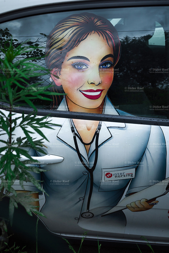 Switzerland. Canton Ticino. Viganello. On a car parked, the drawing of a smiling nurse working for Internursing. Since 1992,  Internursing has been selecting and placing at the disposal of private clients, hospitals, clinics, nursing homes and senior residences, healthcare and home-care personnel and care workers. Services are provided 24 hours a day - 365 days a year and, with extreme professionalism, Internursing collaborates with all home health care and care worker providers, also offering the possibility of combined private-assistance management, with prompt spitex interventions, together with care workers or home-care staff. Internursing is a member of the Swiss Private Spitex Association (ASPS), is recognized by SECO, authorized by the Cantonal Medical Department (UMC), and is licensed to provide and place staff throughout Switzerland. Viganello is a quarter of the city of Lugano. 9.06.2020  © 2020 Didier Ruef