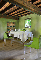 A rustic style dining room with a heavy beamed ceiling and green walls. Two green Philippe Starck Mademoiselle chairs stand near a table covered with a white tablecloth.