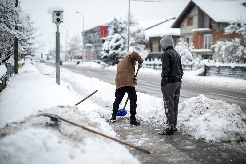 """People from Bira camp trying to clean the footpath from the very dangerous ice.<br /> <br /> Usman Ali from Pakistan.<br /> <br /> Bihać, Bosanska Krajina, Bosnia, 15/12/2018.The Bira camp is a former fridge factory located outside Bihac. It is managed by the UN (ONU) agency called IOM (OIM) - International Organization for Migration. The camp is a huge hangar and it composed by tents and containers (mainly located in the area dedicated to most vulnerable people and families) 'donated' by the EU, Turkkizilayi, Crveni Kriz Grada Bihaca. The camp has got also a Health clinic, the """"Klinika"""", provided by DRC Danish Refugee Council and UNHCR and EU (UE). The People met outside the Klinica who showed their medical refers, their wounds and injuries claimed that they were beaten up by the Croatian Police which also allegedly stole their money and broke their smartphones after they were found trying to cross the border between Bosnia & Croatia, the beginning of the so called """"The Game"""" (1.). The very dangerous end of the """"Balkan route"""", the undetected border crossing throughout Croatia and then Slovenia, which people try numerous times to reach Italy or Austria. If they caught crossing any of the borders, they will be deported back to Bosnia, at """"square 1 of the Game"""".<br /> Clothes, food and a little bit of entertainment for the Children are provided by the Crveni Kriz Grada Bihaca, the Bosnian Red Cross, which also manages a sort of canteen.<br /> The IOM (OIM) provided data about the People living in the Bira camp while this reportage was made:<br /> -2067 people are the inhabitant of the camp (but obviously the number changes a lot and often)<br /> -187 unaccompanied minors all boys, mostly from Pakistan;<br /> -80 families: 325 family members, 145 children, 78 boys, 67 Girls.<br /> Moreover, the IOM (OIM) informed journalists that 550 People will go to the Borici camp when it's restructured and refurbished, mainly the most vulnerable people: families and unaccompanied m"""