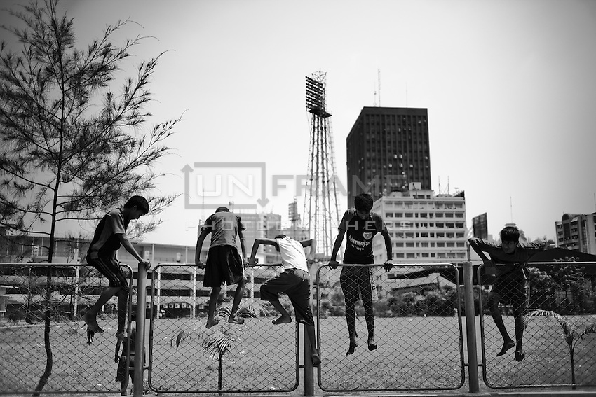 A group of young boxers climb over a fench nearby the Dhaka Stadium.