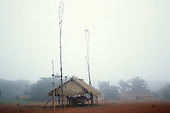 A-Ukre Village, Brazil. The centre of the village with the nobe (men's hut) in the misty dawn. Xingu.