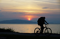 Pictured: A cyclist travels on the Oystermouth path as the sun rises over Kilvey Hill in Swansea, as seen from West Cross in south Wales, UK. Wednesday 21 June 2017<br />