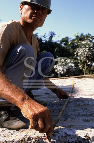 Rio de Janeiro, Brazil. Silva Areal quarry; worker in hard hat measuring rock using a wooden folding rule.