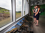 LEAD, SD - JUNE 30: Mikaela Fundaun and Carolyn Weber look over the exhibit space near the large windows overlooking the open cut mining area during the Sanford Lab Homestake Visitor Center Grand Opening Tuesday in Lead, S.D. (Photo by Richard Carlson/dakotapress.org)
