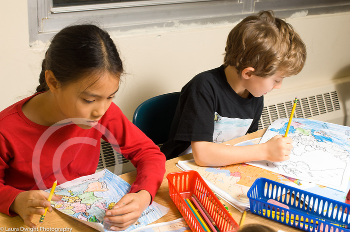 Education elementary school Grade 3 male and female students working on map making project, working separately