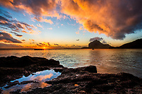 Last sunrays on Le Morne Brabant mountain and the Indian Ocean, with a colorful sunset sky reflecting in a lava tide pool, Mauritius Island, Africa