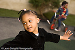 Preschool backyard playground children playing in early spring ages 3-5 New York City girl in motion looking to side horizontal