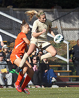 Boston College midfielder Kate McCarthy (21) plays through the ball. University of Miami defender Allie Rossi (4)..After two overtime periods, Boston College (gold) tied University of Miami (orange), 0-0, at Newton Campus Field, October 21, 2012.