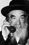 Making a  phone call .  At a Jewish Hasidic wedding  in Stamford Hill, London