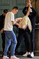 Pictured: A young woman is helped to her feet in Swansea. Tuesday 31 December 2019 to Wednesday 01 January 2020<br /> Re: Revellers on a night out for New Year's Eve in Wind Street, Swansea, Wales, UK.