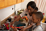 Mother in kitchen with 10 year old son, food preparation, boy peels raw carrot as mother washes strawberries