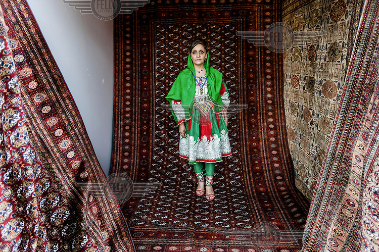 An Afghan woman sells carpets in the exhibition at Kabul /Felix Features