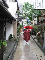 Geisha walks down a narrow street in  Pontocho - Kyoto, Japan