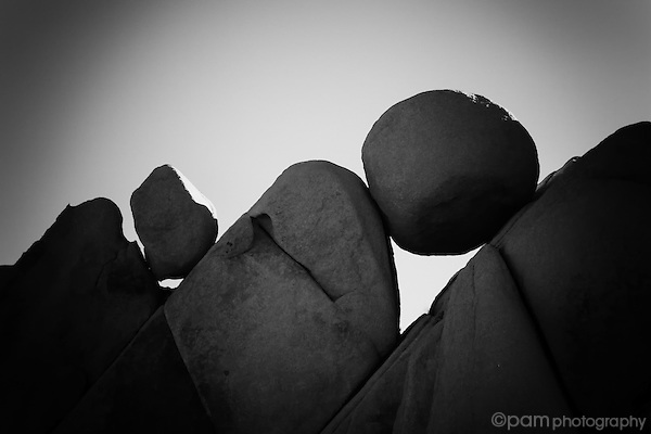 Black and white of round rocks balancing between angular rocks