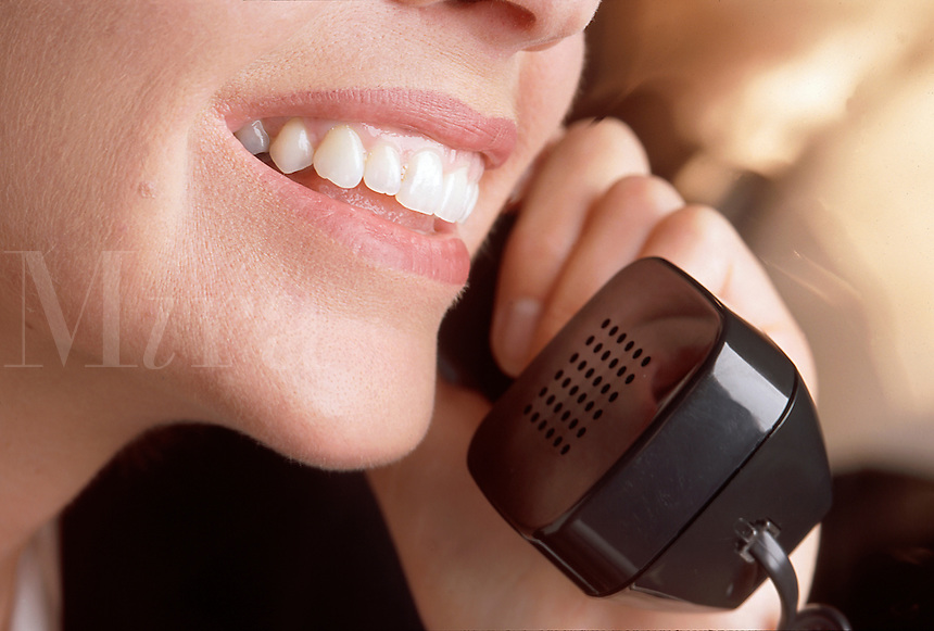 A smiling woman talking on the phone.