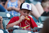 A young Winston-Salem Dash fan enjoys a slice of pepperoni pizza during the game against the Greensboro Grasshoppers at Truist Stadium on August 13, 2021 in Winston-Salem, North Carolina. (Brian Westerholt/Four Seam Images)
