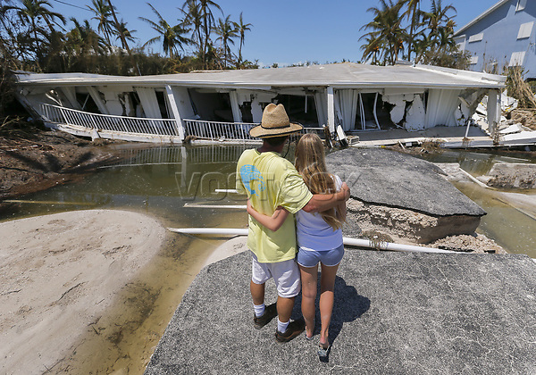 epaselect epa06201191 Mike Gilbert (L) hugs his daughter Brooke (R) while looking at a destroyed three-story condominium building after Hurricane Irma struck the Florida Keys in Islamorada, Florida, USA, 12 September 2017. The Gilbert family owns a unit in the building. Many areas that sustained damage during the storm remain under a dawn to dusk curfew.  EPA-EFE/ERIK S. LESSER