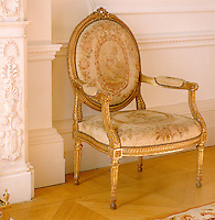 In a grand entrance hall an antique armchair with a faded floral silk cover is situated next to an ornate fireplace