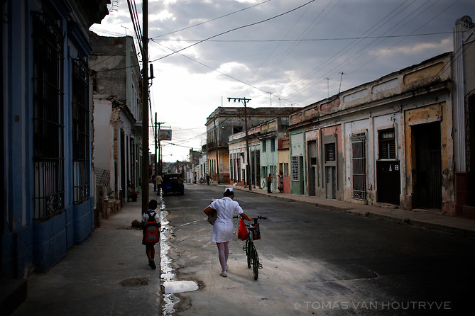 A nurse pushes her son's bicycle as he walks along side in Cienfuegos, Cuba on 17 March 2009.