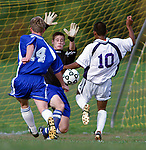 North Brunswick's goalie Josh Schanen gets his hands up to block the shot of Monroe's # 10 (right)--Oswaldo Delgado, as North Brunswick's # 14 (left)--Weston Pearson coming in to help defend on the play during the 1st half of play at Monroe.