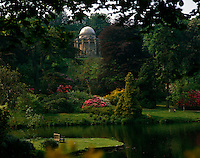 View over the tranquil lake and rhododendrons to the magnificent Temple of Apollo at Stourhead