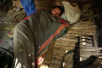 Fathi Ja lies under a blanket in his hut in a hidden temporary village in the Vientiane province of Laos on 28 November 2007. Fathi Ja's wife and two children were killed two months earlier during a raid by the Lao People's Army. Thousands of Hmongs who fought or collaborated with the American CIA until communists took over the country in 1975 remain hidden in the jungles of Laos and are regular targets of the Lao People's Army
