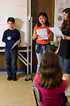 Public school Grade 6 boy and two girls making presentation in science class differing heights vertical