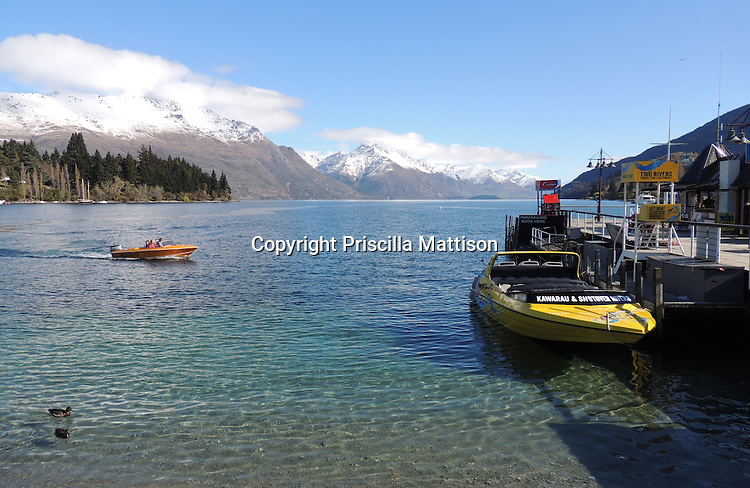 Queenstown, New Zealand - September 12, 2012: Two motorboats share Lake Wakatipu with ducks.