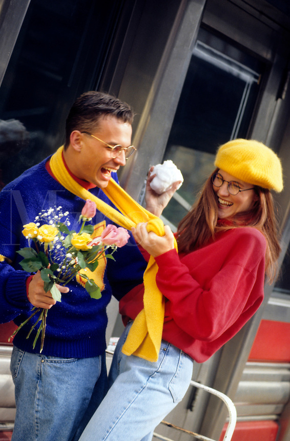 Couple having fun with snow ball and flowers in winter sweaters in front of diner and colorful.