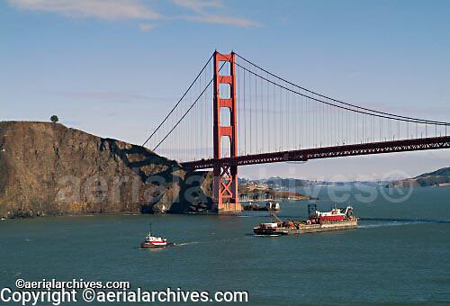 aerial photograph tug boat pulling loaded barge under Golden Gate bridge California