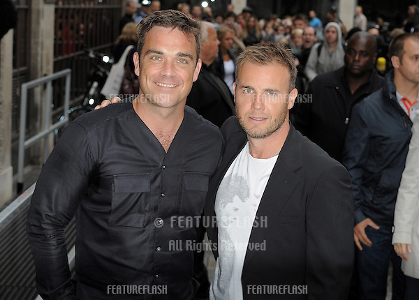 Robbie Williams and Gary Barlow leave Radio 1 after promoting their single Shame on the Chris Moyles show..London. 26/082010. Picture by: Simon Burchell / Featureflash