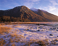 Evening light on Ben Starav, tipped with snow, seen from Glen Etive where the valley-floor is covered in the ice-sheets from a flooded then frozen river; Scottish Highland