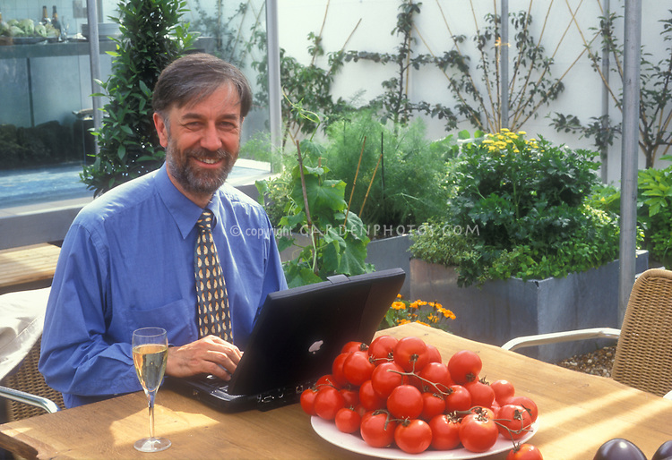 British Garden Writer Graham Rice working in garden at table with computer mac laptop with glass of champagne wine, bowl of red tomatoes in Terence Conran designed rooftop garden at the Chelsea Flower Show