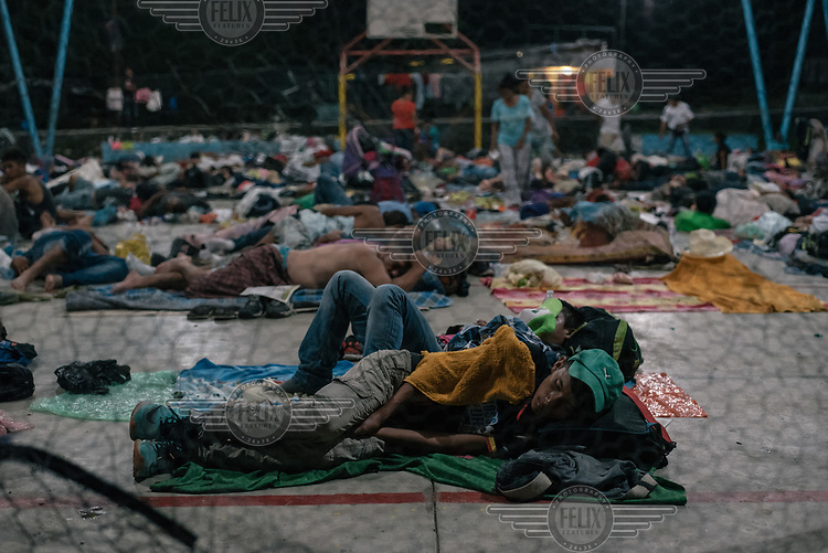 A group of Central American refugees rest for a night on a basketball court.