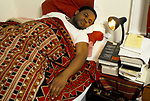 Sousa Jamba, Angolan novelist & journalist. He was about to write a story for the Telegraph Magazine on Hunting. Seen here on his bed site in south London. He  were running late!