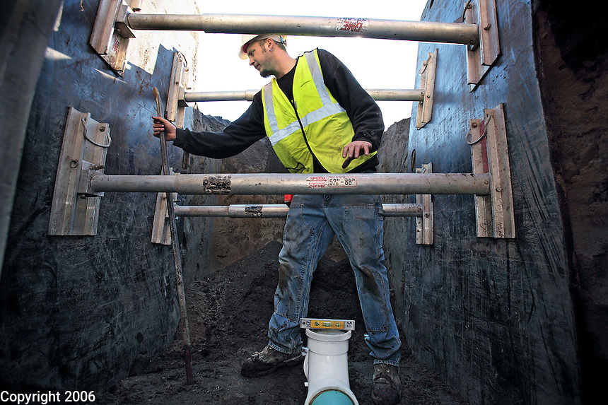 """Pipe layer Jon Daniels installs underground sewer pipe for Looker & Associates, Inc. Daniels is working within the protective confines of a """"trench box,"""" a huge steel box that prevents the dirt walls of an excavated trench from collapsing and burying workers in soil."""