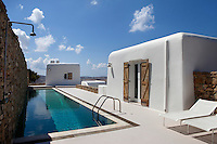 luxury pool area with white deck chairs