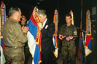 """Yougoslavia. Bosnia. Serbian republic. Bijelina. Radovan Karadzic (C) and General Ratko Mladic (L). Celebration for """"Vidovdan"""" day. Each year on the 28th of June, the serbs celebrate the day of the army. Religious service in the orthodox church. Radovan Karadzic is kissing the serbian flag while the general Ratko Mladic is clapping his hands. Radovan Karadzic was arrested in Belgrade on 21 July 2008. He was extradited to the Netherlands, and is currently in The Hague, in the custody of the International Criminal Tribunal for the former Yugoslavia. General Ratko Mladic is on the list of the International Criminal Tribunal for the former Yugoslavia (ICTY), based in The Hague in the Nederlands, as a most wanted man for war crimes. © 1995 Didier Ruef"""