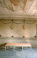 A pair of brass sconces is mounted above a simple bench in the hall which has a stone flagged floor and a painted wood ceiling
