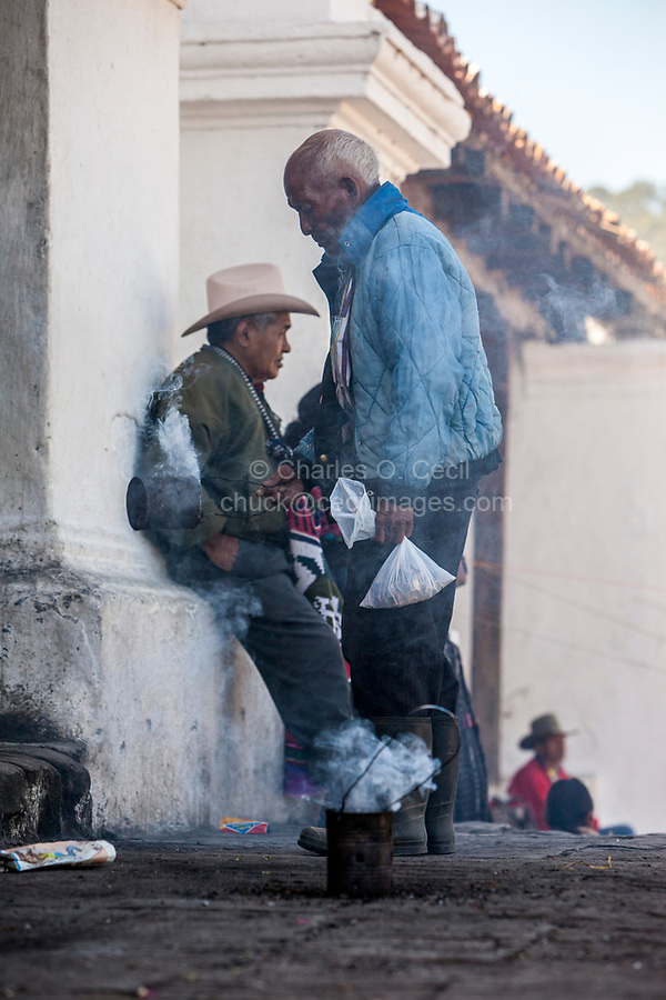 Chichicastenango, Guatemala.  A Cloud of Incense Envelopes a Traditional Quiche Priest as he Swings his Incense Can outside Entrance to Santo Thomas Church, Sunday Morning.