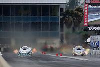 Mar. 11, 2012; Gainesville, FL, USA; NHRA funny car driver Mike Neff (left) races alongside Jim Head during the Gatornationals at Auto Plus Raceway at Gainesville. Mandatory Credit: Mark J. Rebilas-