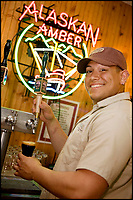 USA, Alaska, Steven Sano pours samples from a tap of Alaskan ale at the brewing company's tasting room and gift shop in Juneau. MR