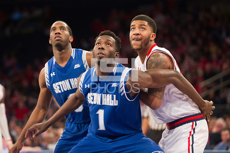 NEW YORK, NY - Sunday December 21, 2015: Khadeen Carrington (#0) of Seton Hall and Michael Nzei (#1) of Seton Hall box out Ron Mvouika (#24) of St. John's as the two teams square off in regular season play at Madison Square Garden.