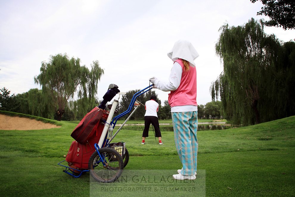 CHINA. A caddie looks on as a golfer prepares to take a shot at the Huatang International Golf Club in Beijing. 2009