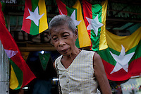 A homeless woman walks past new Burmese flags on sale in a shop in Yangon. The Burmese government introduced the new flag in the lead up to the elections scheduled for 07/11/2010.