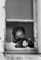 Mostar / Bosnia Erzegovina 1994<br /> Soldato dell'Armija Bosniaca spara dalla finestra del suo appartamento contro le postazioni dell'esercito croato lungo il boulevard, la strada del centro di Mostar diventata prima linea.<br /> Soldier of the Bosnian Army shoot from the window of his apartment against the Croatian army positions along the boulevard, the main street in the center of Mostar became the front line. <br /> Photo Livio Senigalliesi