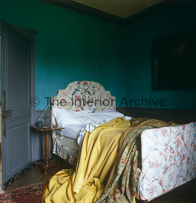 An unmade bed with a chintz-covered frame in a room, painted a turquoise-blue