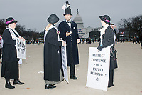 """A man dressed as Abraham Lincoln with a small protest sign reading """"Kiss my Trump"""" poses for pictures at the end of the day after people gathered in the National Mall area of Washington, DC, for the Women's March on Washington protest and demonstration in opposition to newly inaugurated President Donald Trump on Jan. 21, 2017."""