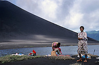 Girl and mother washing clothes on the banks of Siwi Lake, Vanuatu.